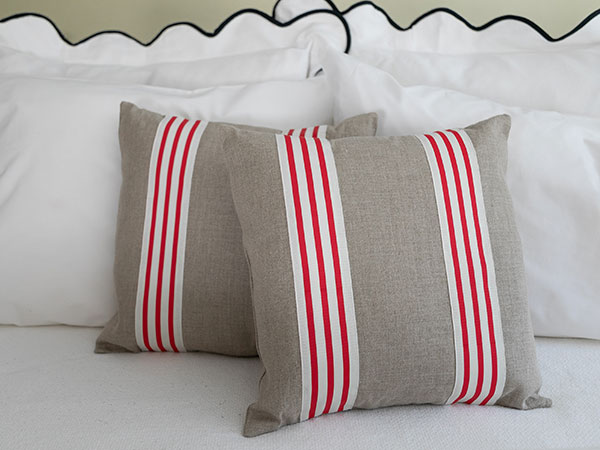 close up of red and white striped pillows