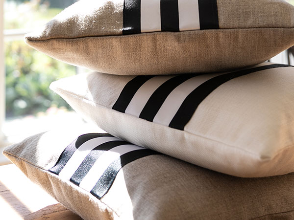 close up of black and whitestriped pillows in sunlight